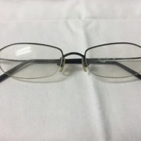 18.  A pair of small rectangular black wire framed glasses.