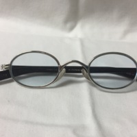 19.  A pair of medium blue-tinted ovular wire framed glasses with black earpieces.