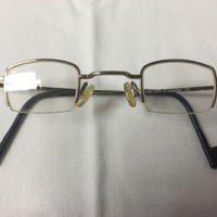 14.  A pair of small rectangular silver wire framed glasses with brown square tipped earpieces.