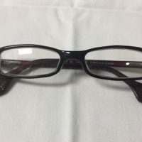 12.  A pair of small rectangular black & red plastic glasses with pentagonal ends on the earpieces.