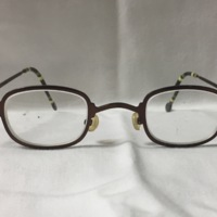 1. A pair of small round brown metal glasses with yellow and green stripes on the round-tipped earpieces.