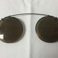 3.  A pair of round clip-on sunglasses meant to attach to a pair of normal glasses.