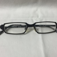 6.  A pair of small rectangular black metal glasses with pyramid shapes near the lenses.
