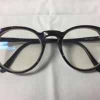 17.  A pair of large circular black purple & gold plastic glasses.